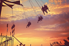 People Riding Rides And Enjoying The Summer Atmosphere At A State Fair At Dusk Toned With A Retro Vintage Filter App Or Action