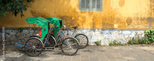 Fotografering  Vietnamese rickshaws (Cyclos) in Hoi An, Vietnam シクロとホイアンの黄色い壁