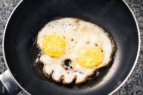Egg in the skull shape frying in the pan with very hot oil, The concept is about side effects and dangers of old frying oil