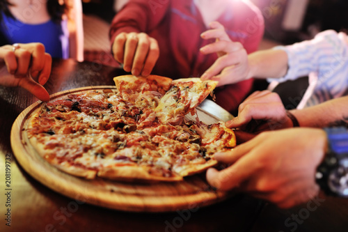 Cadres-photo bureau Pizzeria Hands taking pizza slices from wooden plate