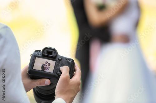 Fototapeta Professional photographer with camera and wedding couple, outdoors obraz na płótnie