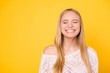 canvas print picture - Portrait with copy space empty place of comic funky girl laughing with clenched teeth keeping eyes closed isolated on yellow background