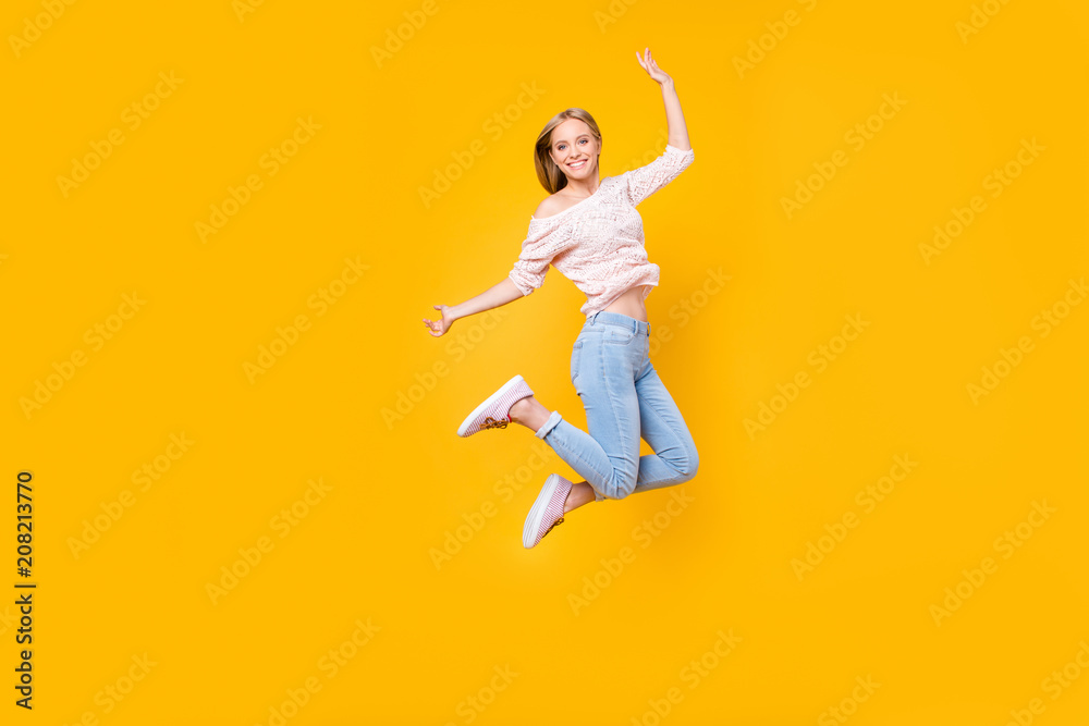 Fototapety, obrazy: Portrait of playful crazy girl jumping in the air looking at camera enjoying weekend having perfect mood isolated on yellow background