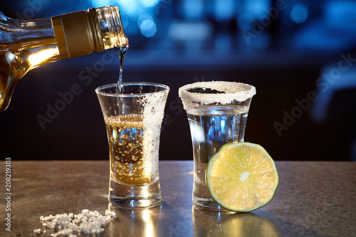 Two glasses with a tequila and a slice of lime.