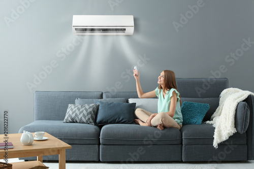 Fototapeta Young woman switching on air conditioner while sitting on sofa at home obraz