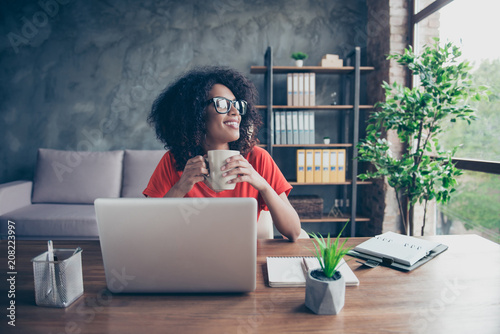 Portrait of dreamy lovely accountant sitting at desk in modern office with interior drinking hot beverage holding cup with tea in hands looking at window enjoying freetime