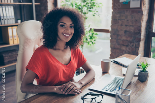 Valokuvatapetti Portrait of trendy charming attorney with beaming smile in casual outfit sitting at desk in modern office looking at camera