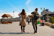 Two girls with stylish coats and backpacks walk in the Park with rides, rear view