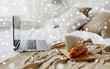 cosy home, interior and winter concept - cozy bedroom with laptop computer, coffee cup and croissant on bed over snow