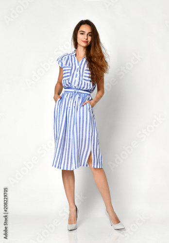 Young beautiful woman posing in new blue stripes casual summer dress on grey  Wall mural