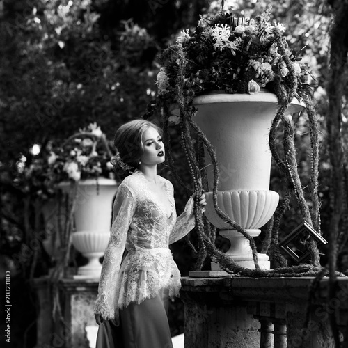 Foto op Plexiglas womenART Elegant female model wearing maxi dress and white lace jacket with long sleeves posing on summer terrace beside classical stone balustrade and large flower vases against green foliage on background.