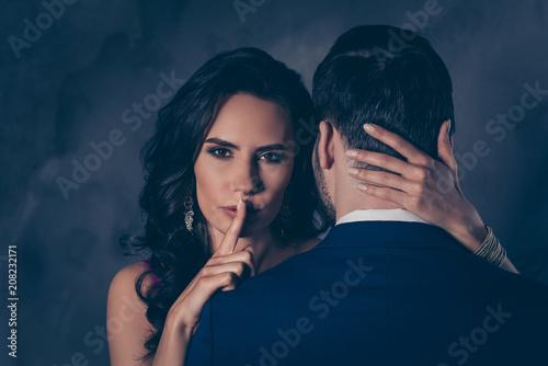 Portrait of pretty charming mrs in purple dress with jewelry half face mr in tuxedo bowtie holding hand in pocket of pants embracing his lover lovely attractive couple isolated on grey background