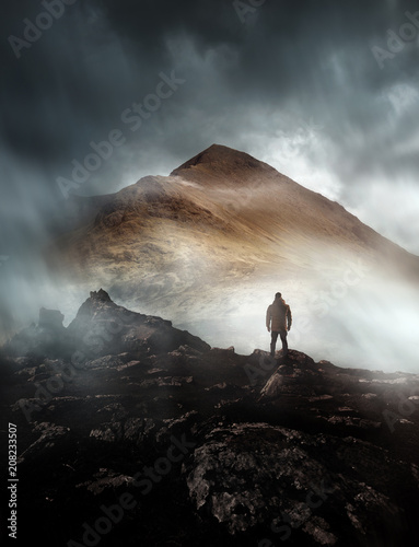 Poster Grijze traf. A person hiking looks onwards at a mountain shrouded in mist and clouds with the peak visible. Scenic landscape photo composite.