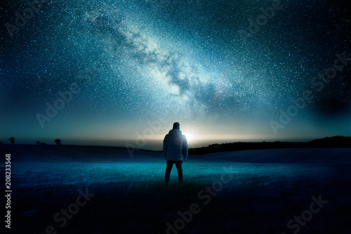 Aluminium Prints Green blue A man stands watching with wonder and amazement as the moon and milky way galaxy fill the night sky. Night time landscape. Photo composite.