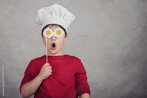 Fotografie, Obraz  niño gracioso con huevos fritos en sus ojos