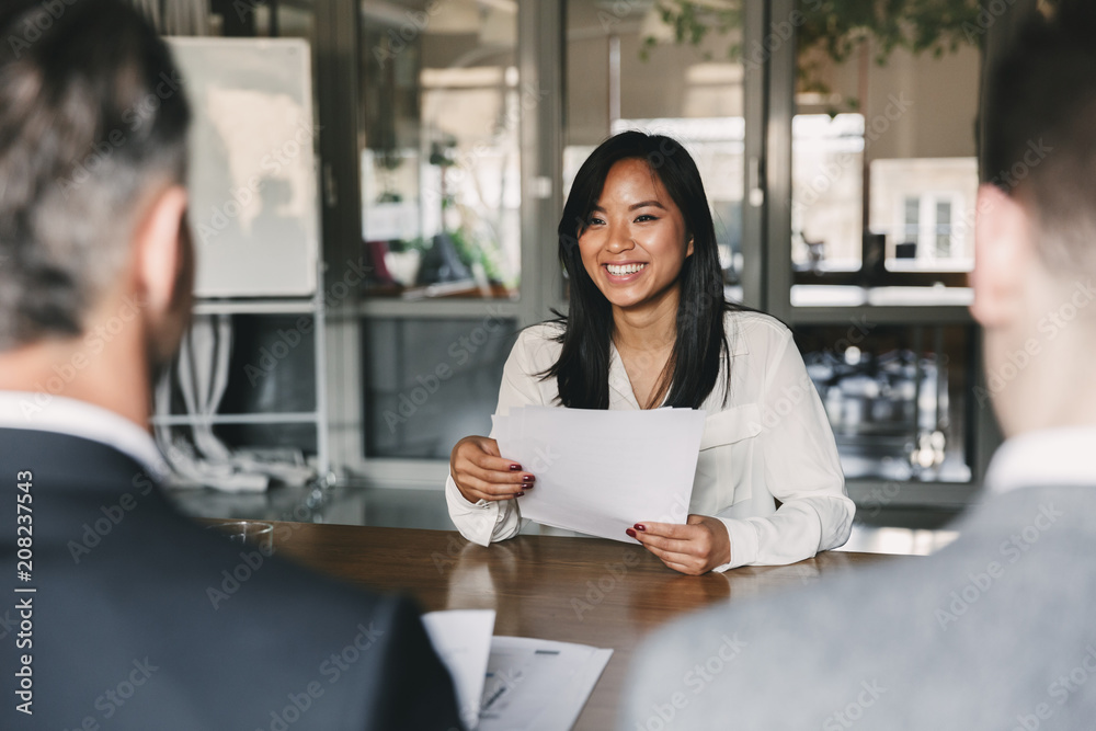 Fototapeta Business, career and placement concept - young asian woman smiling and holding resume, while sitting in front of directors during corporate meeting or job interview