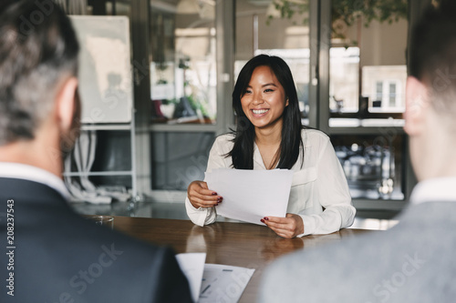 Stampa su Tela  Business, career and placement concept - young asian woman smiling and holding r