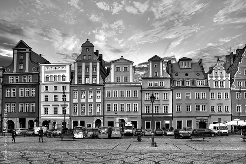 Central market square in Wroclaw Poland with old houses, street lamp and walking tourists people at gorgeous stunning evening sunset sunshine. Travel vacation concept. Black and white