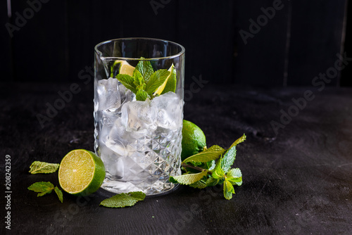 Photo  A big glass for cocktails with ice and mint on black background