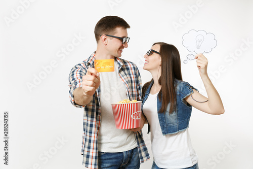 Photo  Young couple, woman and man in 3d glasses watching movie film on date holding bucket of popcorn, say cloud with lightbulb, idea and credit card isolated on white background