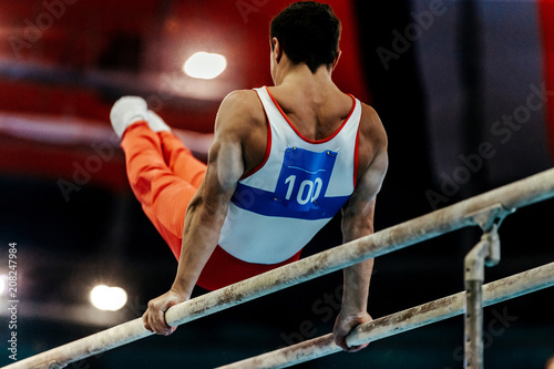 sports gymnastics athlete gymnast exercises on parallel bars