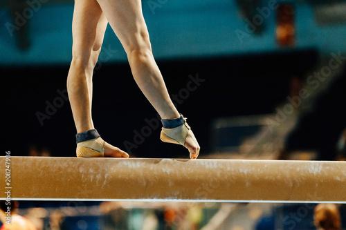 Foto auf Leinwand Gymnastik artistic gymnastics legs women gymnast exercises on balance beam