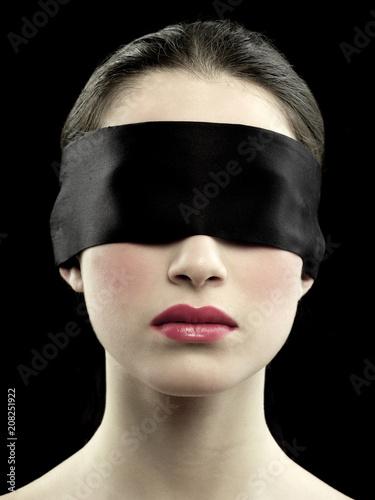 Photo beautiful blindfolded girl on black