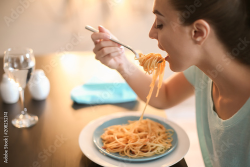 Young woman eating tasty pasta in cafe Fototapeta