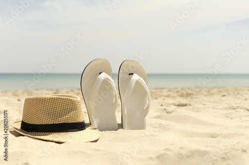 Hat and white flip-flops on the beach with blue sea in the background