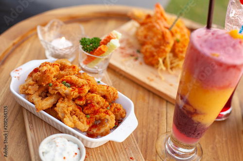 Poster Klaar gerecht Close up to appetizer calamari and fried shrimp on tray with colourful smoothy.