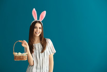 Beautiful Young Woman With Easter Eggs And Bunny Ears On Color Background