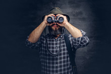 Portrait Of A Bearded Hunter Traveler Tries To Find Prey While Looking Through Binoculars.