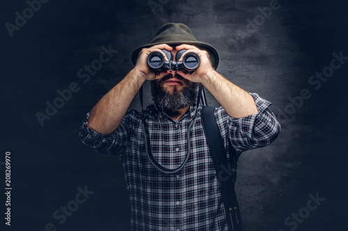 Portrait of a bearded hunter traveler tries to find prey while looking through binoculars Fototapet