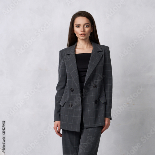 Gorgeous young woman dressed in gray squared jumpsuit, blazer and heeled shoes posing in studio Canvas Print