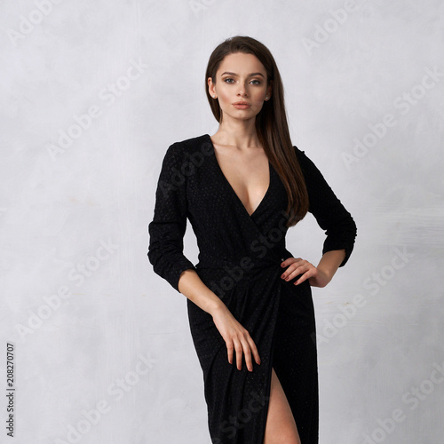 Leinwand Poster Beautiful brunette female model dressed in strapless taupe black formal dress posing in studio