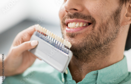 medicine, dentistry and healthcare concept - close up of dentist with tooth color samples choosing shade for male patient teeth at dental clinic - 208274354
