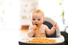 Little Baby Girl Eating Her Spaghetti Dinner And Making A Mess