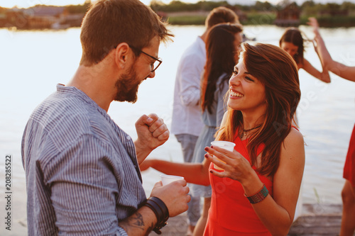 Man and woman flirting at party by the river Tablou Canvas