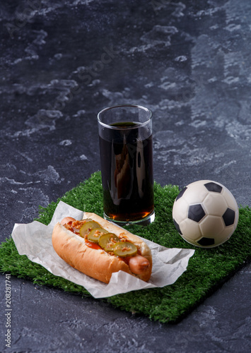 Photo of glass of beer, green grass with soccer ball, hotdog Poster