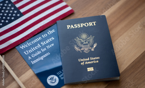 Fototapeta Passport of USA (United states of America) next to a Guide for new Immigrants - Welcome to the United states and American Flag