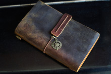 Travel Note On Black Background. Handmade Paper Diary Notebook In Brown Leather Cover. Old Vintage Leather Book, Top View.