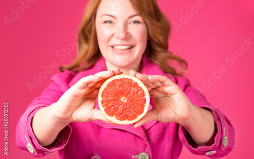 Photographie  Beautiful adult woman, blurred face, holding forward juicy grapefruit
