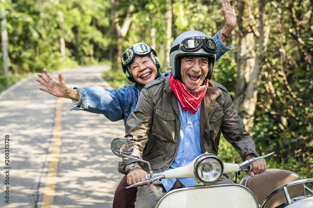 Fototapety, obrazy: Senior couple riding a classic scooter