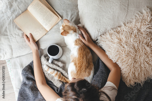 Hygge concept with cat, book and coffee in the bed Fototapet