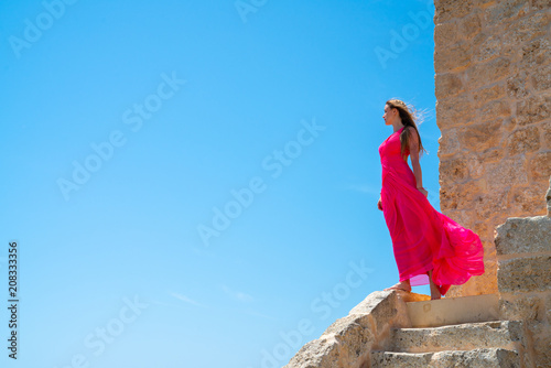 Beautiful girl in a long pink dress standing on the edge of the white cliffs by Fototapeta