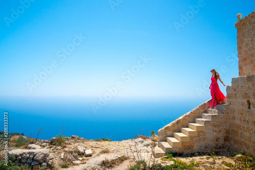 Photo Beautiful girl in a long pink dress standing on the edge of the white cliffs by
