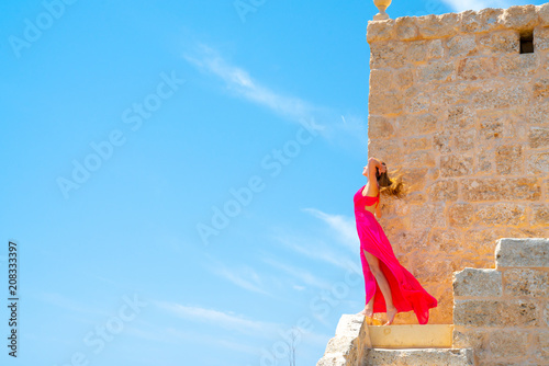 Fotografie, Obraz Beautiful girl in a long pink dress standing on the edge of the white cliffs by