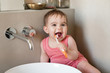 Happy baby holding toothbrush in bathroom