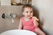 Baby with toothbrush in mouth in the bathroom