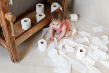 Baby Playing With Toilet Paper Rolls In Bathroom